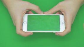 Genom att använda den smarta telefonen på den gröna skärmen med olika handgester, horisontellt, tätt upp - grön skärm stock video