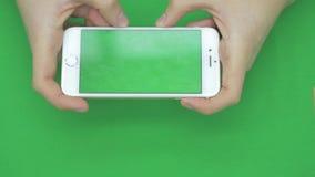 Genom att använda den smarta telefonen på den gröna skärmen med olika handgester, horisontellt, tätt upp - grön skärm arkivfilmer