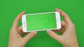 Genom att använda den smarta telefonen på den gröna skärmen med olika handgester, vertikal nära övre - grön skärm arkivfilmer