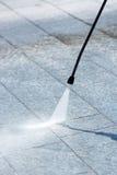 Genom att använda ett tryck vattna med slang för att driva ren stenläggning Fotografering för Bildbyråer