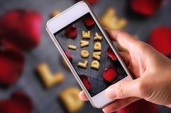 Genom att använda mobiltelefonen för att ta foto av kakaabc:et i form av ordet ÄLSKAR JAG DADY-alfabet med det röda roskronbladet Arkivbilder