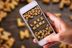 Genom att använda mobiltelefoner för att ta foto av kakaabc:et i form av ordet ÄLSKA MAMMAalfabetet på gammal wood bakgrund, vale Arkivfoton