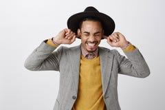 Genom att använda naturliga öronproppar för att inte höra spoiler Snygg lycklig mörkhyad grabb i flott hatt och stilfull dräkt royaltyfri fotografi