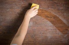 Genom att använda svampen för att göra ren dammigt trä arkivbilder