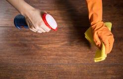 Genom att använda trasan för att göra ren dammigt trä arkivbild