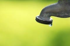 Genomblöt vattenkran med vattendroppe Arkivbild