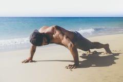 Genomkörareövningsbegrepp Den sunda stiliga aktiva mannen med den muskulösa kroppen för passformen som att göra skjuter, Ups övni Fotografering för Bildbyråer