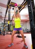 Genomkörare för övning för Crossfit konditionKettlebells gunga på idrottshallen Royaltyfri Foto