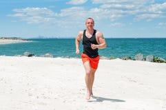 genomkörare Idrotts- manspring på stranden Royaltyfri Bild