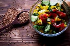 Genomskinlig bunke med en sallad av tomater, gurkor, bulgarisk peppar och gräsplaner Klätt med olivolja på mörker Arkivfoto