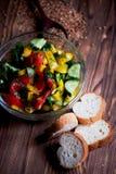 Genomskinlig bunke med en sallad av tomater, gurkor, bulgarisk peppar och gräsplaner Klätt med olivolja på mörker Royaltyfri Foto