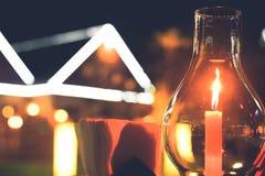 Genomskinlig exponeringsglasstearinljushållare, mörk trägrund som förläggas på en trätabell royaltyfri bild