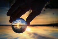 Genomskinlig glass boll som reflekterar en solnedgång Royaltyfri Fotografi