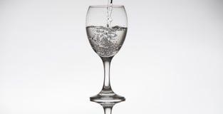 Genomskinlig glass påfyllning med vatten Royaltyfria Bilder