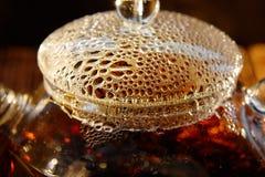 Genomskinlig glass tekanna med svart te på en brun bakgrund Royaltyfri Foto