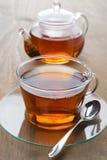 Genomskinlig kopp av svart te och tekannan på en träbakgrund Arkivbilder