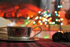 Genomskinlig kopp te i en stålkopphållare på bakgrunden av en brinnande spis och julgirland royaltyfri fotografi
