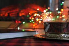 Genomskinlig kopp te i en stålkopphållare på bakgrunden av en brinnande spis och julgirland arkivbild