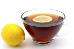 Genomskinlig kopp te med en skiva av citronen och hel citronvänstersida som isoleras på vit Royaltyfria Foton