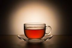 Genomskinlig kopp te på en bakgrund av vita fläckar Royaltyfri Foto