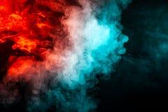 Genomskinlig tjock rök, exponerad av ljus mot en mörk bakgrund som delas in i två färger: blått och rött, brännskador ut, fotografering för bildbyråer