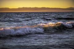 Genomskinlig våg på solnedgången arkivbilder