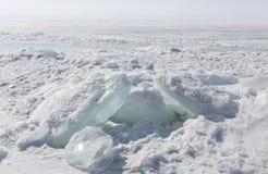 Genomskinliga blåa ismindre kulle på den Lake Baikal kusten Sikt för Sibirien vinterlandskap Snö-täckt is av sjön bifokal arkivbild