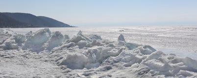 Genomskinliga blåa ismindre kulle på den Lake Baikal kusten Sikt för Sibirien vinterlandskap Snö-täckt is av sjön bifokal royaltyfri bild