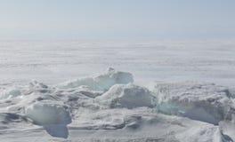 Genomskinliga blåa ismindre kulle på den Lake Baikal kusten Sikt för Sibirien vinterlandskap Snö-täckt is av sjön bifokal arkivfoto