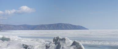 Genomskinliga blåa ismindre kulle på den Lake Baikal kusten Sikt för Sibirien vinterlandskap Snö-täckt is av sjön bifokal fotografering för bildbyråer