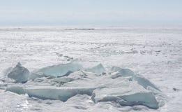 Genomskinliga blåa ismindre kulle på den Lake Baikal kusten Sikt för Sibirien vinterlandskap Snö-täckt is av sjön bifokal royaltyfria bilder