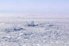 Genomskinliga blåa ismindre kulle på den Lake Baikal kusten Sikt för Sibirien vinterlandskap Snö-täckt is av sjön bifokal arkivbilder