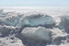 Genomskinliga blåa ismindre kulle på den Lake Baikal kusten Sikt för Sibirien vinterlandskap Snö-täckt is av sjön bifokal royaltyfria foton