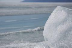 Genomskinliga blåa ismindre kulle på den Lake Baikal kusten Sikt för Sibirien vinterlandskap Snö-täckt is av sjön bifokal arkivfoton