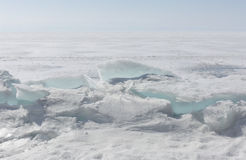 Genomskinliga blåa ismindre kulle på den Lake Baikal kusten Sikt för Sibirien vinterlandskap Snö-täckt is av sjön bifokal royaltyfri foto