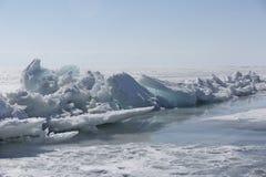Genomskinliga blåa ismindre kulle på den Lake Baikal kusten Sikt för Sibirien vinterlandskap Snö-täckt is av sjön bifokal royaltyfri fotografi