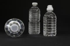 Genomskinliga dricksvattenflaskor Arkivbild