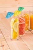 Genomskinliga exponeringsglas med citrusfrukter och fruktsaft Arkivfoto