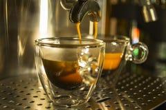 Genomskinliga glass koppar av espresso som är förberedd i en espr Arkivfoto