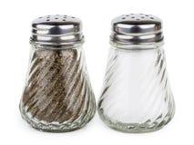 Genomskinliga glass shaker med salt och peppar Royaltyfri Fotografi