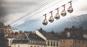 Genomskinliga kabelbilar som anknyter bastillen med stadscenen royaltyfri foto