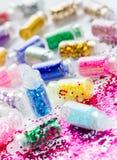 Genomskinliga små flaskor med blänker makeup och spikar konst Arkivfoton