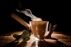 Genomskinligt exponeringsglas av ett läckert varmt kaffe på den mörka bakgrunden arkivbild