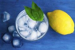 Genomskinligt exponeringsglas med kallt vatten Iskuber i vattnet Blått bakgrund och vatten arkivbild