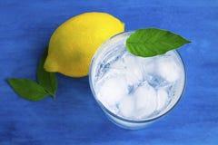 Genomskinligt exponeringsglas med kallt vatten Iskuber i vattnet Bl?tt bakgrund och vatten royaltyfri foto