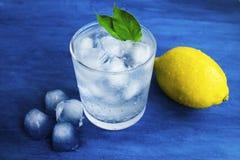 Genomskinligt exponeringsglas med kallt vatten Iskuber i vattnet Bl?tt bakgrund och vatten royaltyfri bild