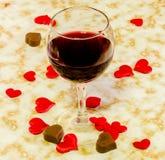 Genomskinligt exponeringsglas med rött vin, hjärtachoklad och röda valentinhjärtor för textil, gammal pappers- bakgrund, slut upp Royaltyfri Foto