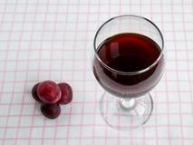 Genomskinligt exponeringsglas med rött vin och få söta röda druvor på den vita rosa rutiga bordduken Bekl?da besk?dar royaltyfri bild
