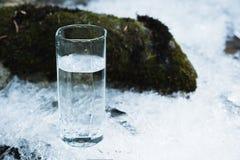 Genomskinligt glass exponeringsglas med att dricka bergvatten i vinter står på en iskall skorpa mot bakgrunden av en rengöring Royaltyfria Bilder