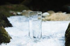 Genomskinligt glass exponeringsglas med att dricka bergvatten i vinter står på en iskall skorpa mot bakgrunden av en rengöring Fotografering för Bildbyråer